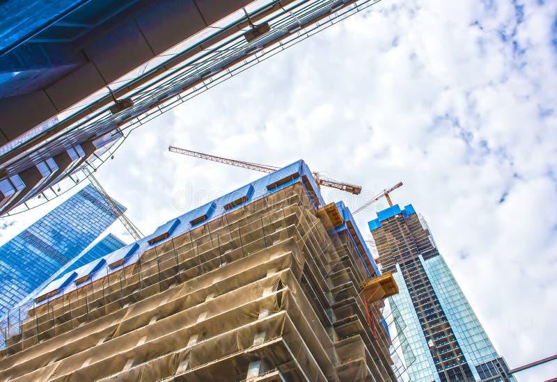 多层的大厦建设中和起重机 免版税库存照片