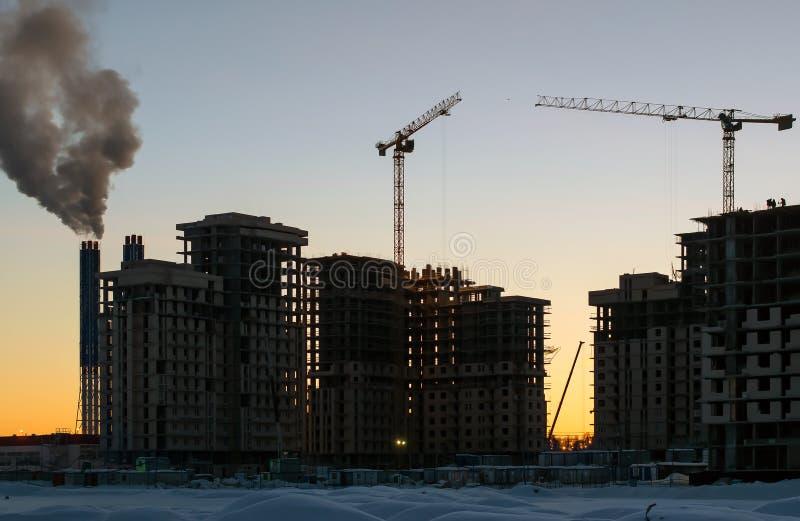 多层的房子的建筑在黑暗的冬天在黎明日落的晚上与起重机 免版税图库摄影