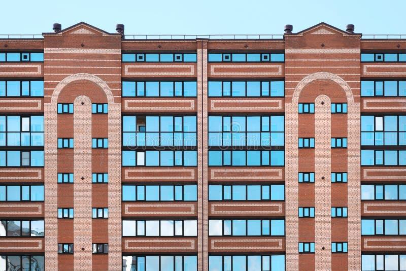 多层的现代房子特写镜头 砖砌,窗口,天空的反射在玻璃的 白天,太阳 免版税库存图片