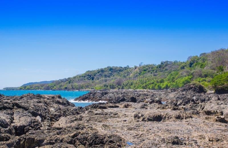 多岩石的海滩和树美好的风景在Playa Montezuma在华美的蓝天和晴天 免版税图库摄影