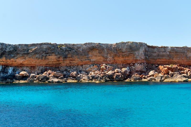 多岩石的海滩和绿松石水 免版税图库摄影