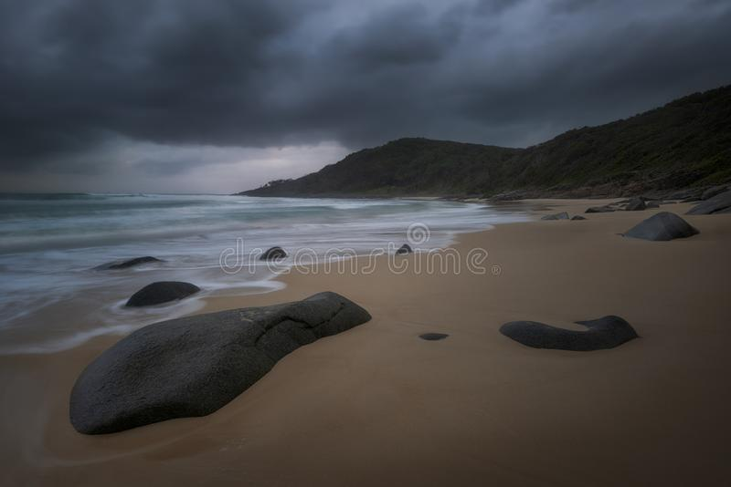 多岩石的海滩在一多云天 免版税库存图片