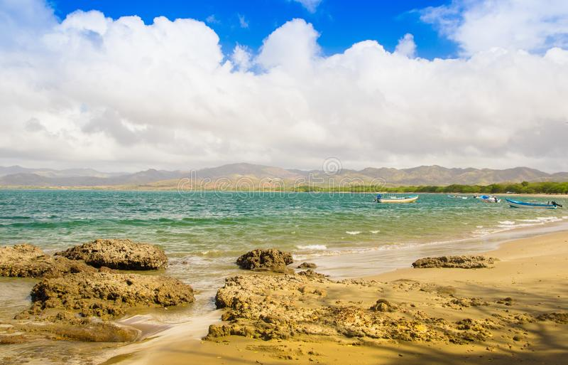 多岩石的海滩美好的室外看法在Montezuma,华美的晴天和绿松石水和蓝天的与一些 库存图片