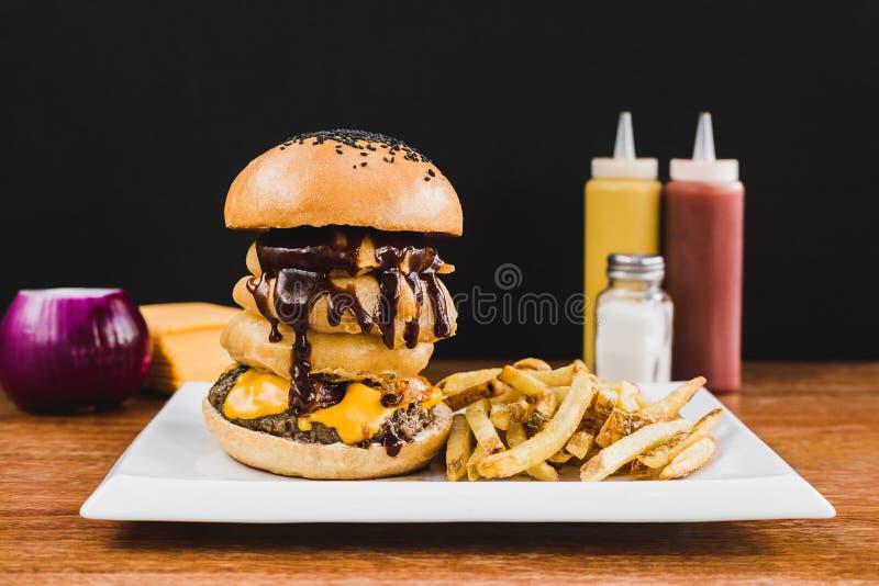 多布尔汉堡用doble切达干酪、莴苣、烟肉、蘑菇和薯条 免版税库存图片