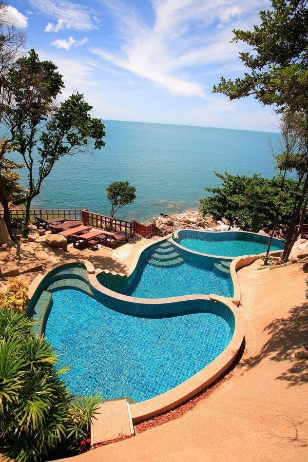 多平实海视图游泳池、太阳懒人在庭院旁边和蓝色海洋 免版税库存图片