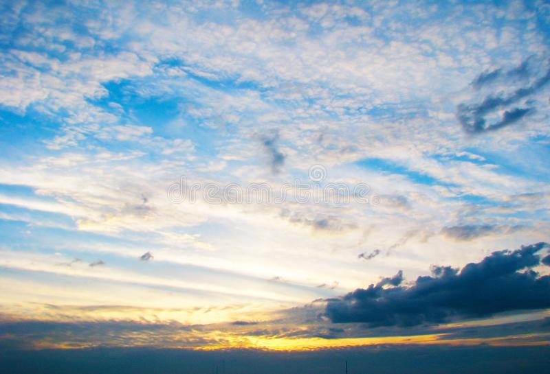 多彩多姿的云彩,照亮由落日,创造一个美好的意想不到的看法 免版税库存照片