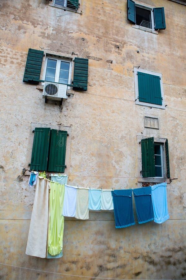 多彩多姿的亚麻布被烘干一个老房子的窗口外 免版税图库摄影
