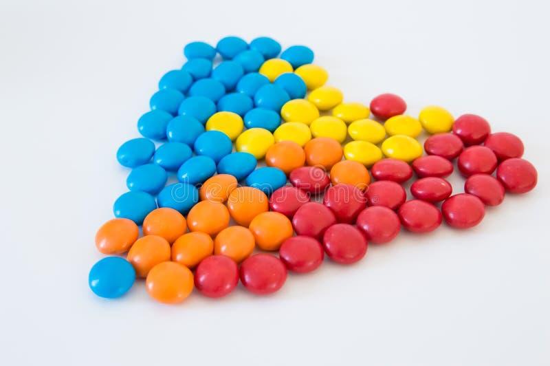 多彩多姿的圆的糖果糖衣杏仁被计划以在白色背景的心脏的形式 库存图片