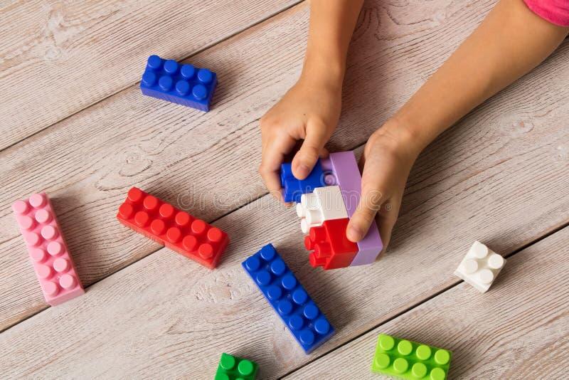 多彩多姿的塑料建设者在女孩的手上 儿童` s教育比赛 图库摄影
