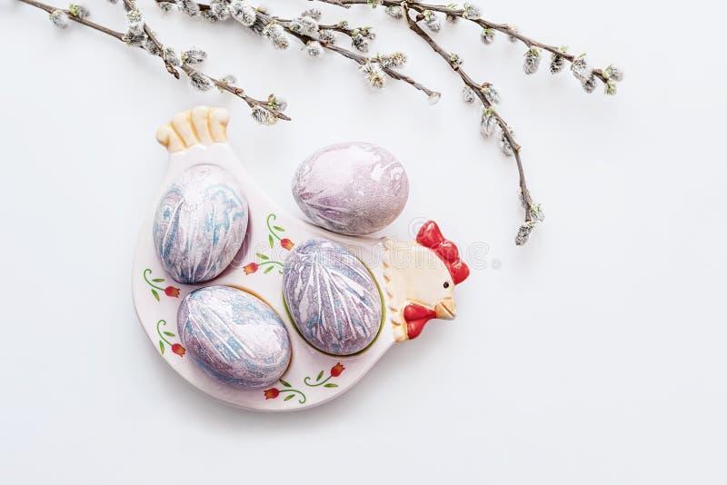 多彩多姿的复活节彩蛋在板材说谎以在轻的背景的一只鸡的形式与杨柳分支花束  库存照片