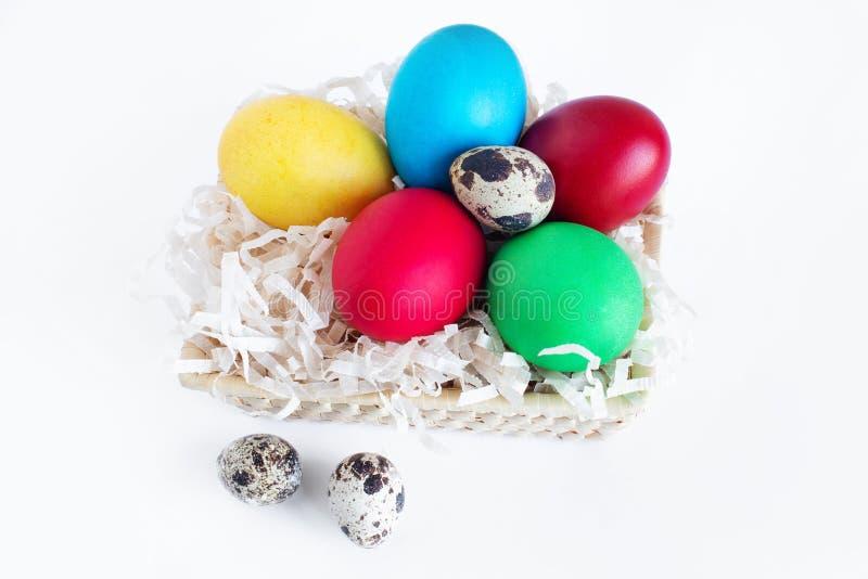 多彩多姿的复活节彩蛋在白色背景的一个篮子在 在篮子的黄色,红色,绿色和鹌鹑蛋 库存照片