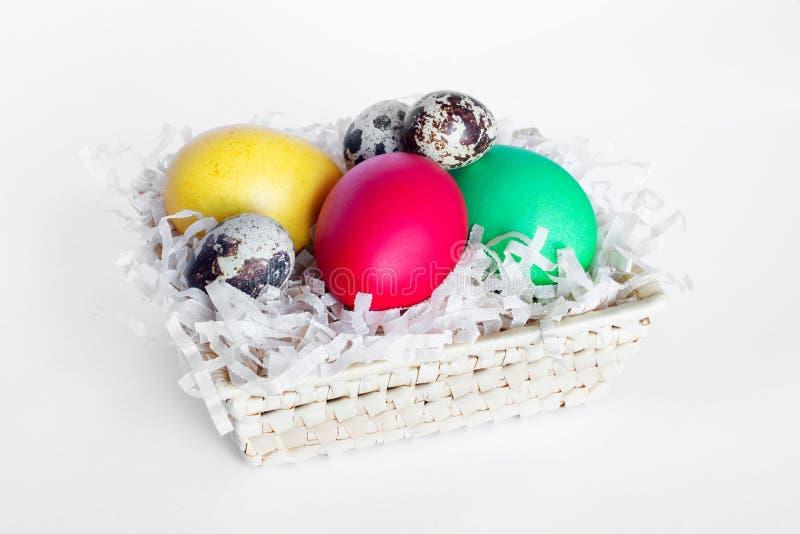 多彩多姿的复活节彩蛋在白色背景的一个篮子在 黄色,红色,绿色和鹌鹑蛋i 库存照片
