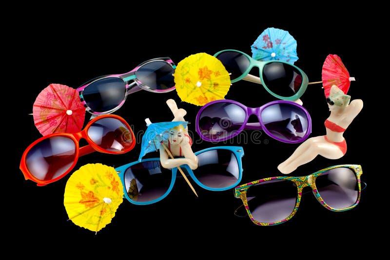 多彩多姿的太阳镜、伞和瓷小雕象在a 免版税库存照片