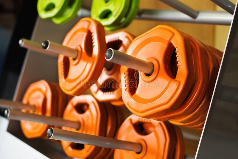 多彩多姿的小型条信号薄煎饼在健身房的金属钉称 图库摄影