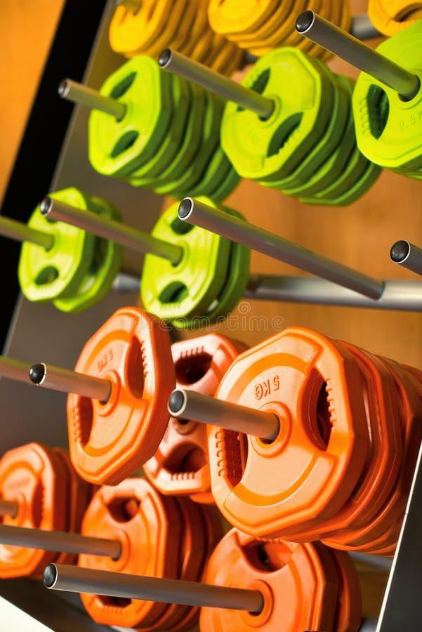 多彩多姿的小型条信号薄煎饼在健身房的金属钉称 免版税库存照片