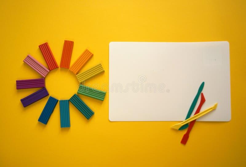 多彩多姿的彩色塑泥片断孩子的反对黄色背景 库存照片