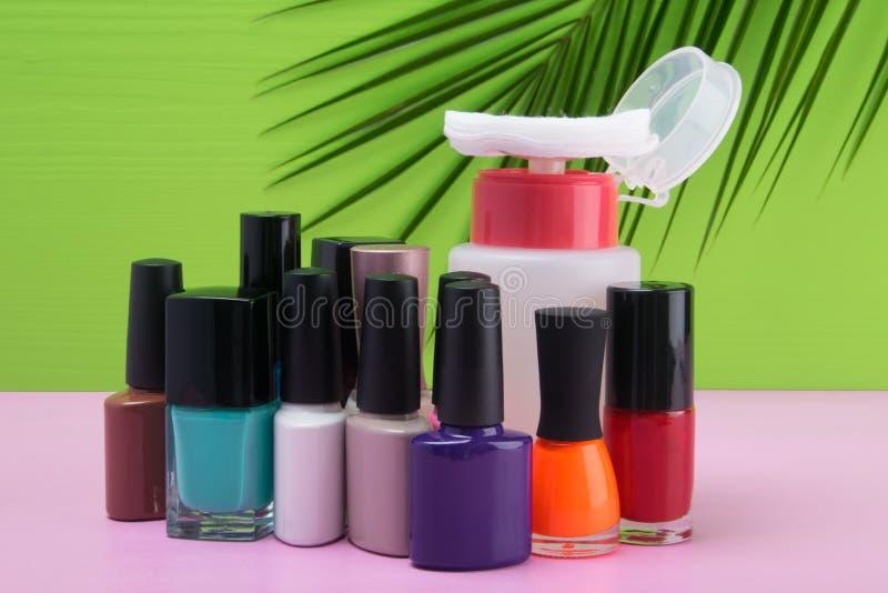 多彩多姿的指甲油在一张桃红色桌上,在与棕榈叶的绿色背景和与化装棉的构成去膜剂 免版税图库摄影