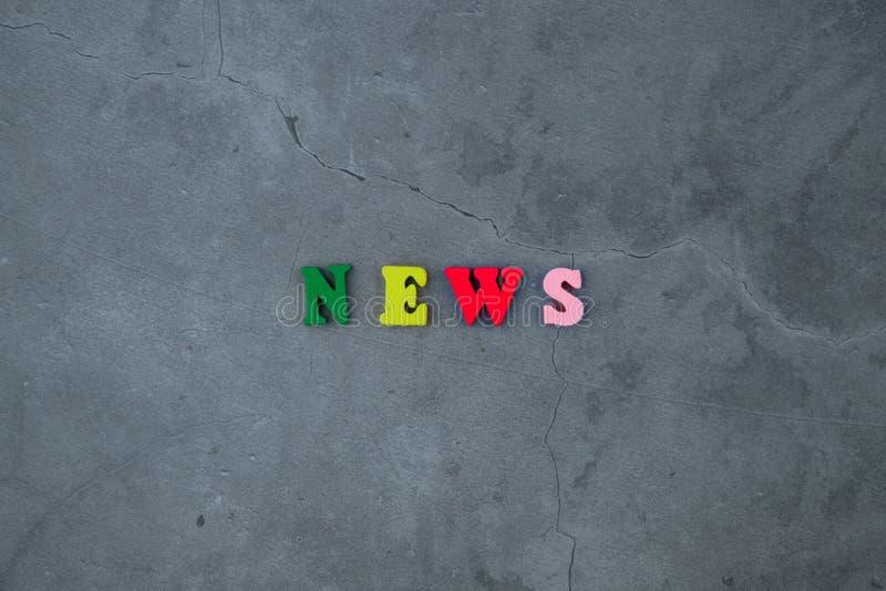 多彩多姿的新闻词由木信件做成在灰色涂灰泥的墙壁背景 免版税库存图片
