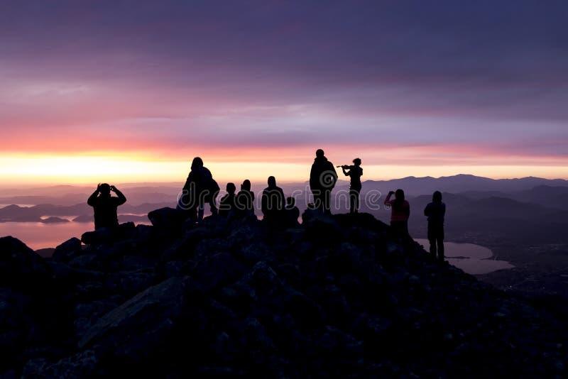 多彩多姿的日落 一名妇女的剪影有小提琴的 人剪影在俯视海的山顶部的 免版税库存照片