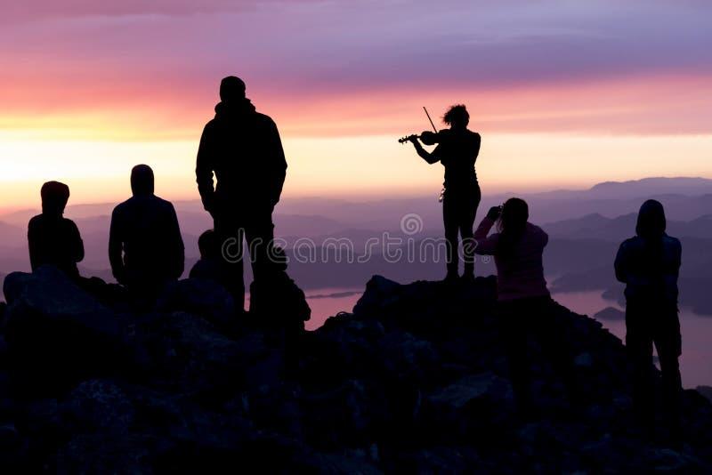 多彩多姿的日落 一名妇女的剪影有小提琴的 人剪影在俯视海的山顶部的 图库摄影