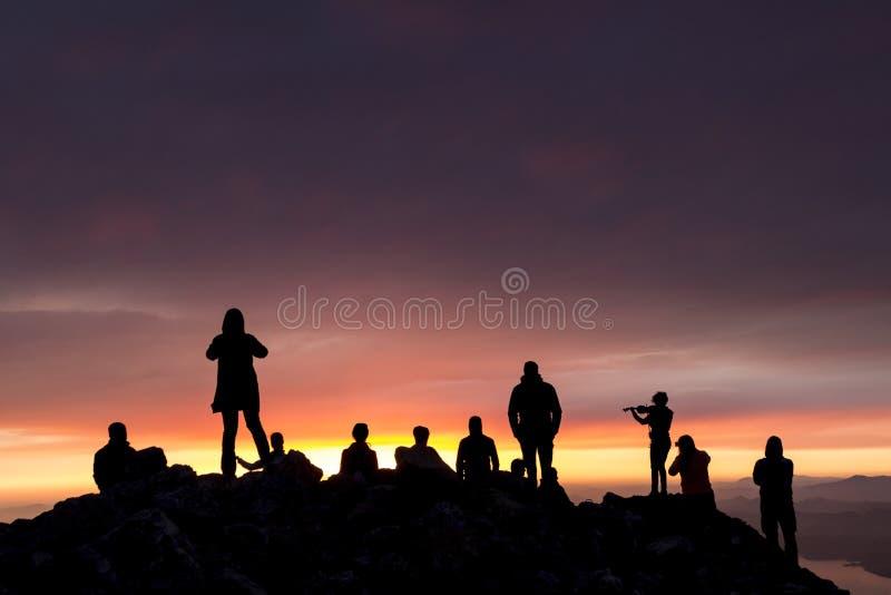 多彩多姿的日落 一名妇女的剪影有小提琴的 人剪影在俯视海的山顶部的 免版税图库摄影