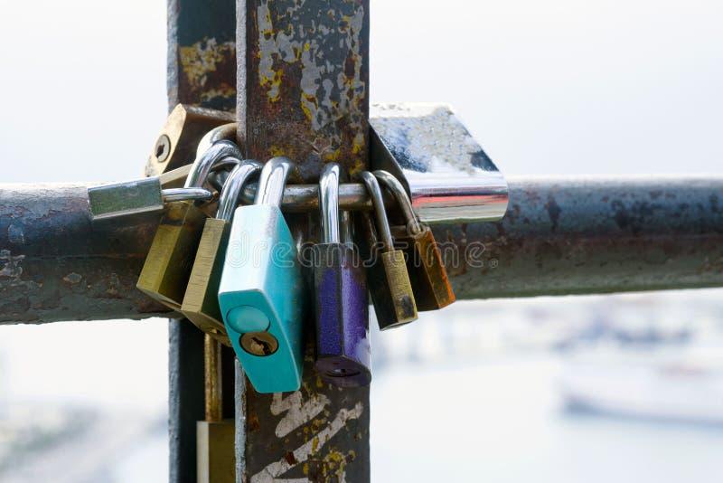 多彩多姿的爱锁,锁在一个生锈的管子 爱和忠诚的标志 免版税库存照片
