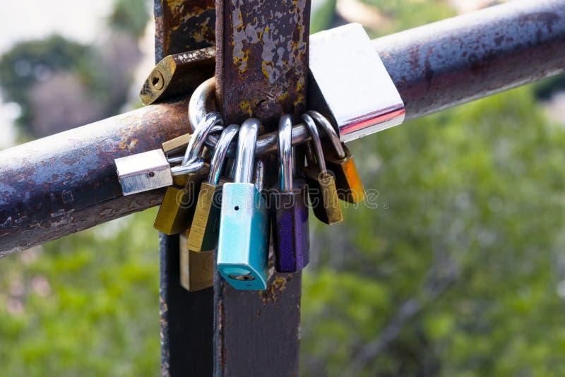 多彩多姿的爱锁,锁在一个生锈的管子 爱和忠诚的标志 库存照片