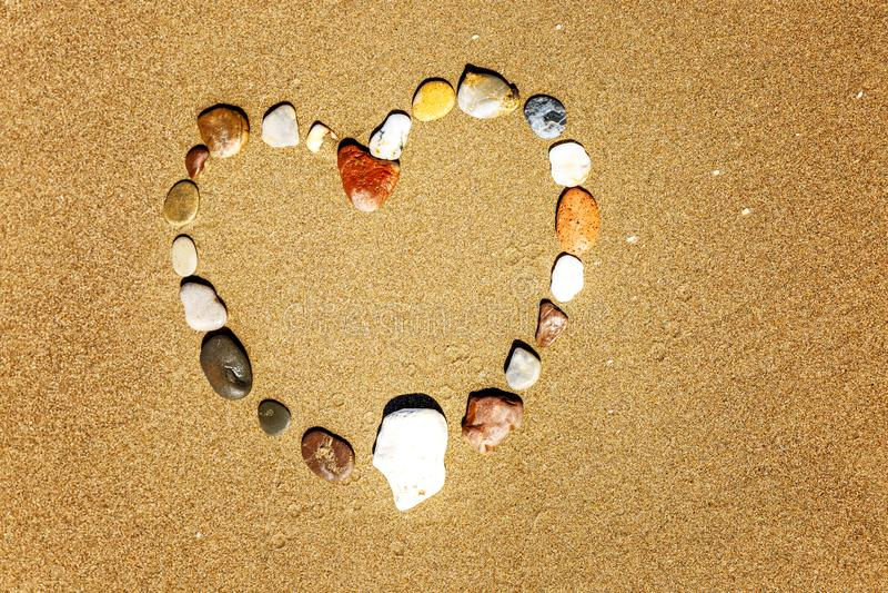 多彩多姿的石头的心脏在一个沙滩的 r ?? r 库存照片