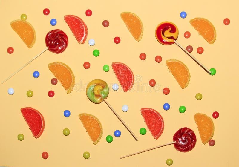 多彩多姿的糖衣杏仁、棒棒糖和橘子果酱切片在黄色背景的柠檬, 图库摄影