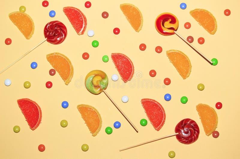 多彩多姿的糖衣杏仁、棒棒糖和橘子果酱切片在黄色背景的柠檬, 库存图片