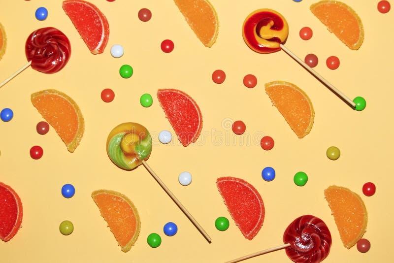 多彩多姿的糖衣杏仁、棒棒糖和橘子果酱切片在黄色背景的柠檬, 免版税库存图片