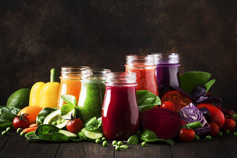 多彩多姿的素食主义者蔬菜汁和圆滑的人从蕃茄,红萝卜,胡椒,圆白菜,菠菜,甜菜根在玻璃瓶 库存照片