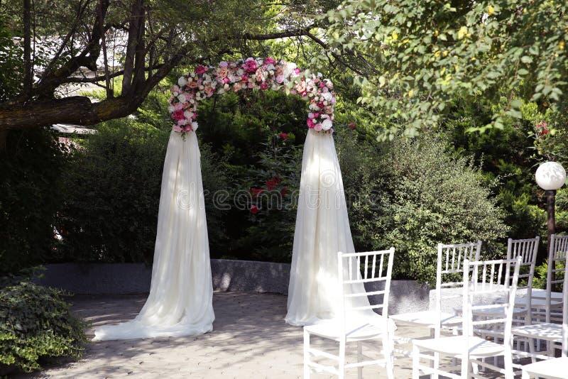 多彩多姿的花和玫瑰婚姻的曲拱与空中丝织物新娘和新郎立场的在一棵绿色树下 库存图片