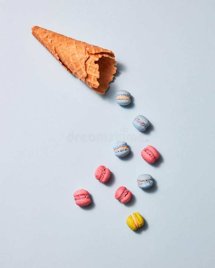 多彩多姿的蛋白杏仁饼干和奶蛋烘饼锥体在灰色背景提出了 平的位置 免版税图库摄影