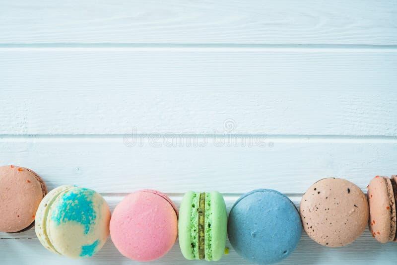 多彩多姿的蛋白杏仁饼干或macaron在一个白色木背景特写镜头,杏仁饼行在桌,拷贝空间上 免版税库存图片