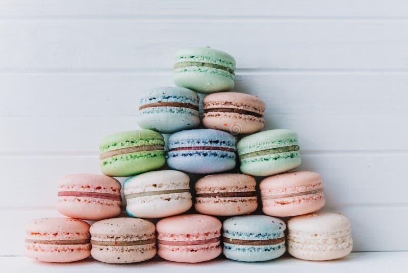 多彩多姿的蛋白杏仁饼干,在淡色口气的杏仁饼金字塔在白色木背景的 免版税库存图片