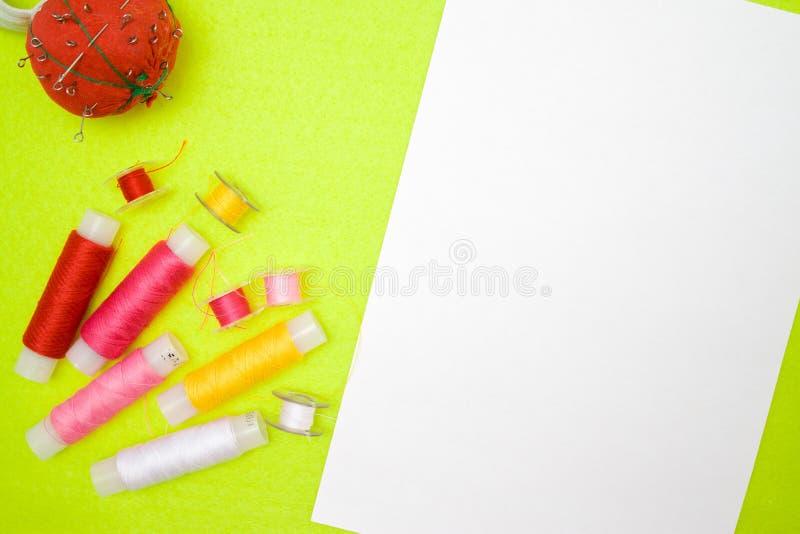 多彩多姿的螺纹卷在绿色背景的红色桃红色黄色白色和测量的磁带 缝合的供应和辅助部件针的 库存照片