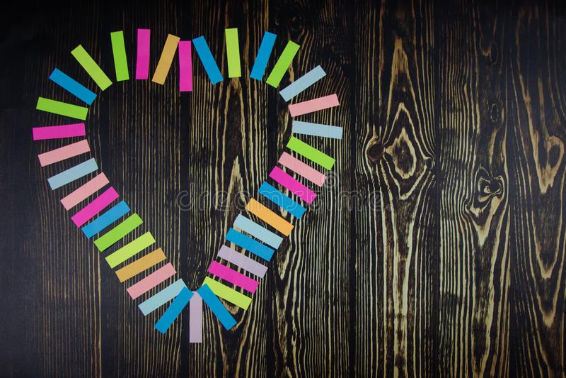 多彩多姿的贴纸的心脏 在深蓝木桌背景 日s华伦泰 看板卡重点爱形状华伦泰 免版税库存照片