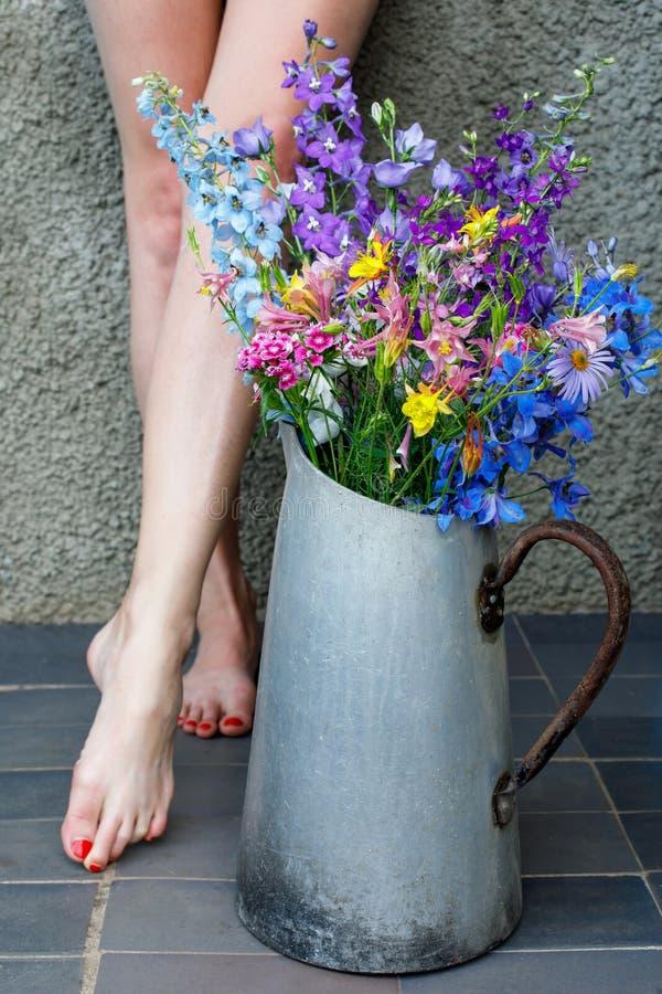多彩多姿的野花花束在一个老金属水罐的以女性腿为背景 免版税图库摄影