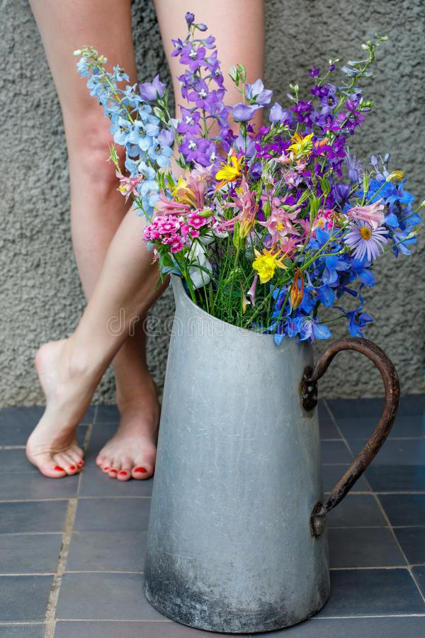多彩多姿的野花花束在一个老金属水罐的以女性腿为背景 免版税库存照片