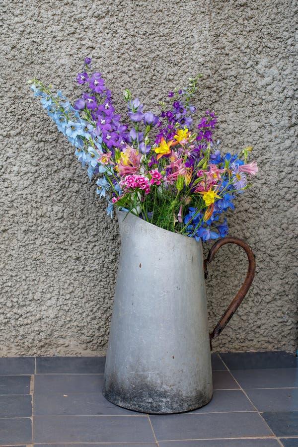 多彩多姿的野花花束在一个老金属水罐的 图库摄影