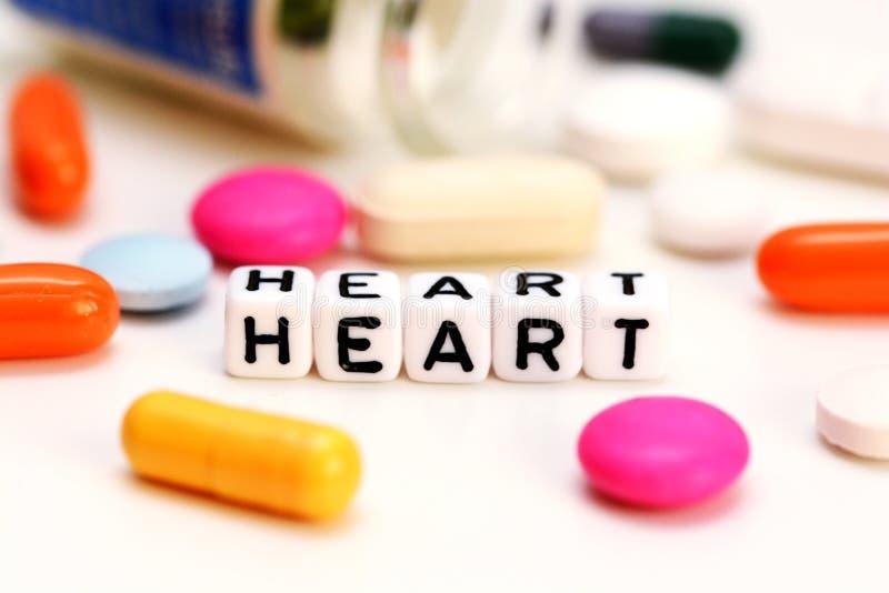 多彩多姿的医疗药物和拼写心脏的信件立方体,建议心脏病问题 免版税库存图片