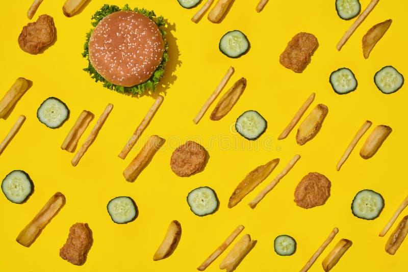 多数普遍的快餐 鸡块、汉堡和炸薯条在黄色背景顶视图 免版税库存图片