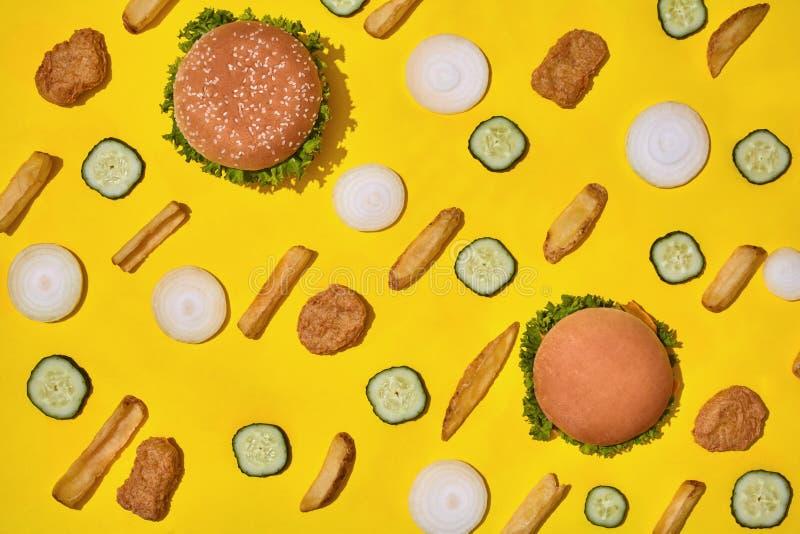 多数普遍的快餐 鸡块、汉堡和炸薯条在黄色背景顶视图 库存照片