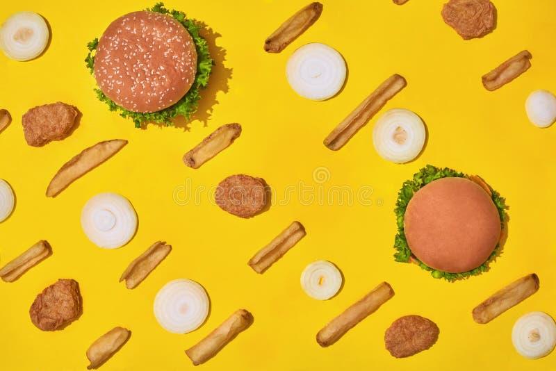 多数普遍的快餐 鸡块、汉堡和炸薯条在黄色背景顶视图 免版税图库摄影