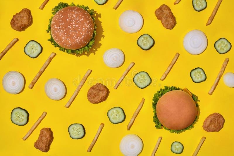 多数普遍的快餐 鸡块、汉堡和炸薯条在黄色背景顶视图 免版税库存照片