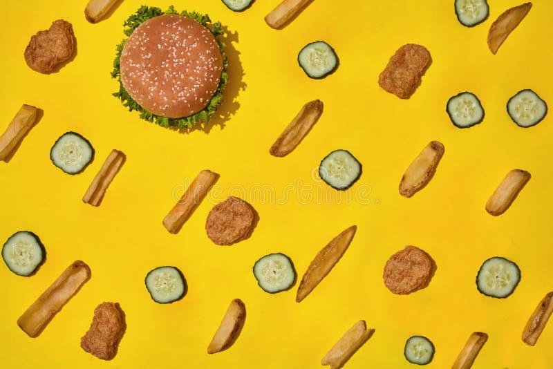 多数普遍的快餐 鸡块、汉堡和炸薯条在黄色背景顶视图 库存图片