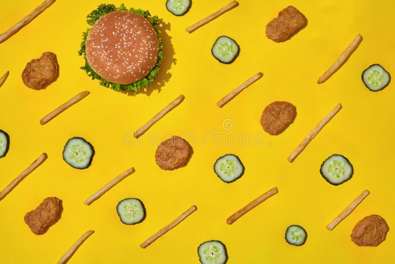多数普遍的快餐 鸡块、汉堡和炸薯条在黄色背景顶视图 图库摄影