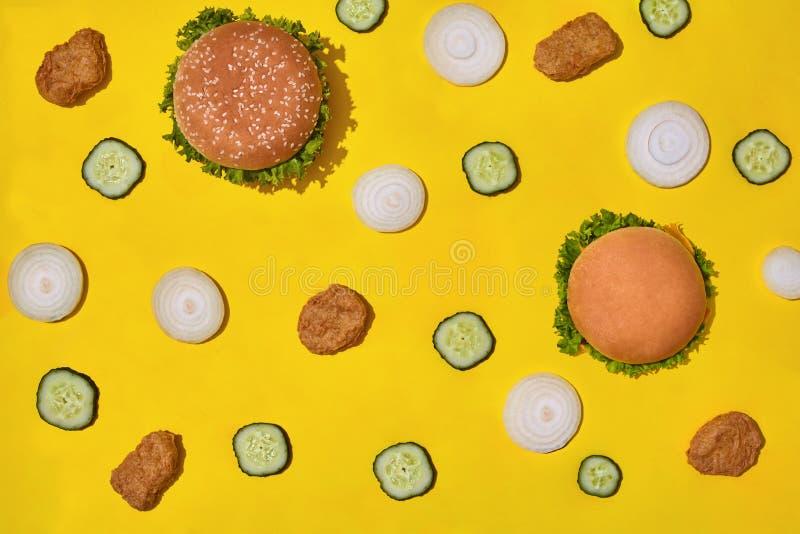 多数普遍的快餐 鸡块、汉堡用新鲜的黄瓜和葱在黄色背景顶视图 免版税图库摄影