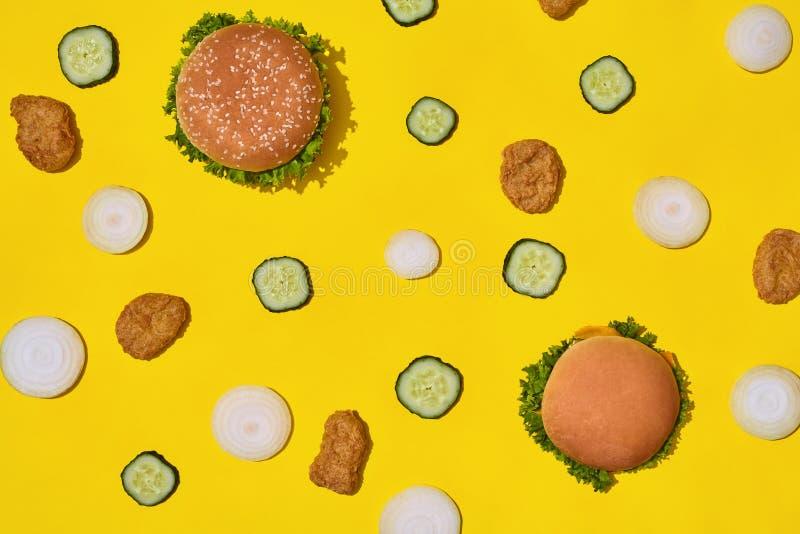 多数普遍的快餐 鸡块、汉堡用新鲜的黄瓜和葱在黄色背景顶视图 免版税库存图片